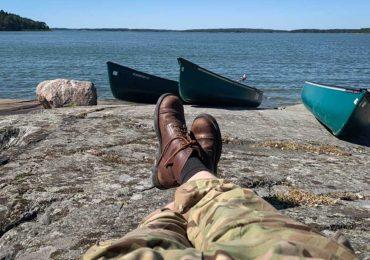 kanootteja kallioluodolla ja lepäävän retkeilijän jalat